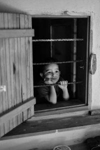 kisgyerek kinéz az ablakon
